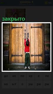 мальчик подошел к дверям и хочет их открыть, но закрыто на замок