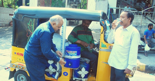 Indian auto rickshaw driver serving cold water