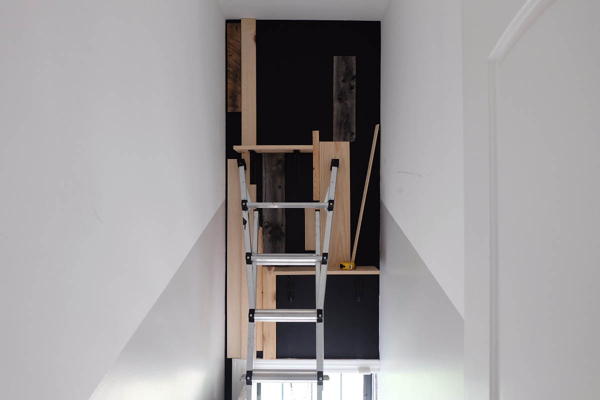 tacking wood pieces to black painted wall
