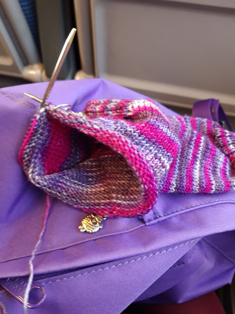 A photo of purple and pink striped knitted sock on a small circular knitting needle.  The sock is resting on a purple rucksack and the colours match very well.