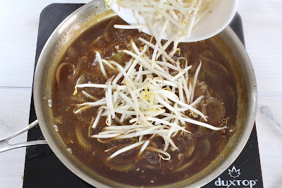 Broth being poured into a pan of cooked onions and celery