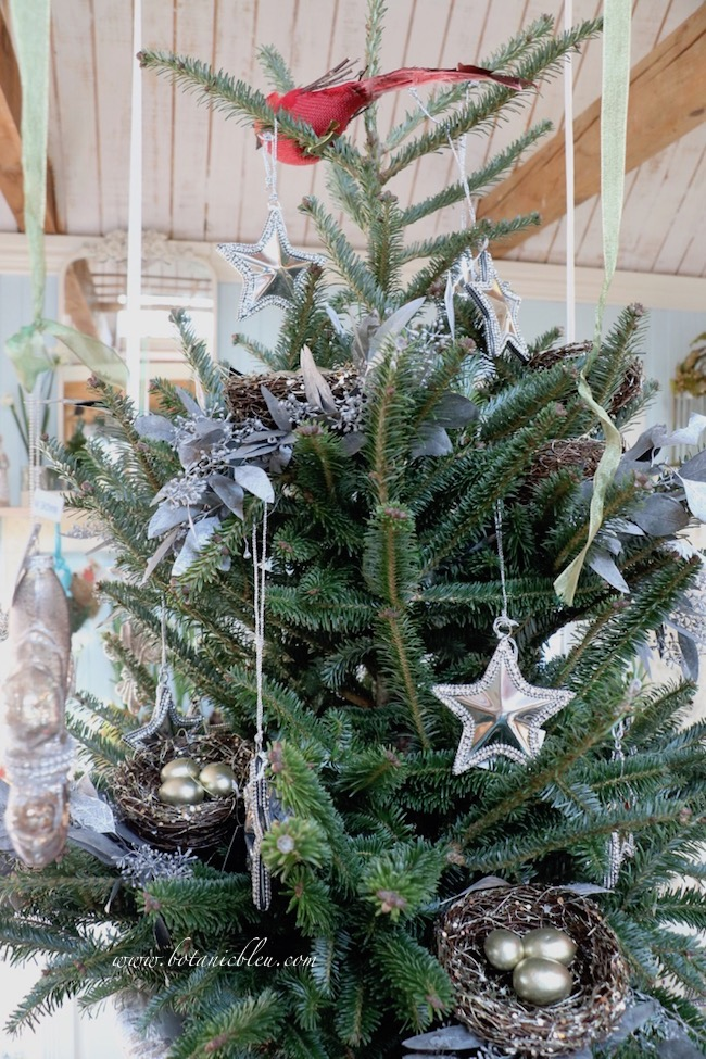 Silver metal stars with rhinestones coordinate with glittered bird's nests on the Christmas tree.