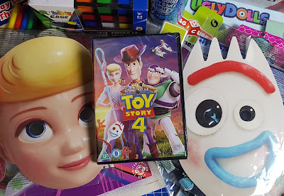 Toy Story 4 DVD and masks on top of random toys and paper