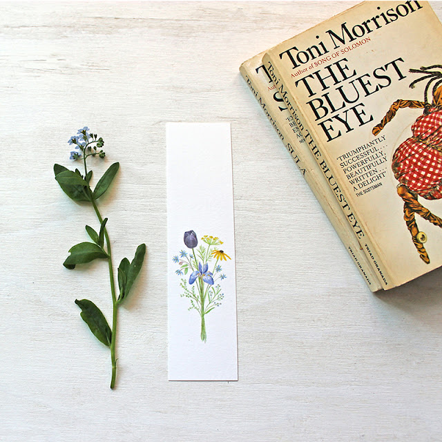 A paper bookmark with a bouquet in watercolor and a worn copy of The Bluest Eye by Toni Morrison