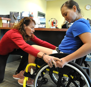 An OT kneels in front of a pediatric client, showing her proper technique for propelling her yellow, manual wheelchair. The OT, wearing a red top, places her hands on the rims of the wheelchair. The client, wearing a light blue top, watches and places her hands on the rims.