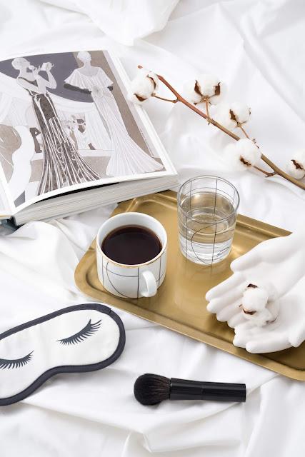 flat lay avec plateau café, un masque pour dormir, un magazine..