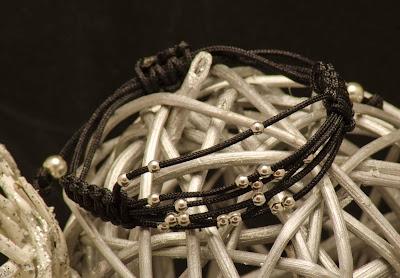 Pulsera de bolas de plata, montada en nylon negro, con terminales en plata.