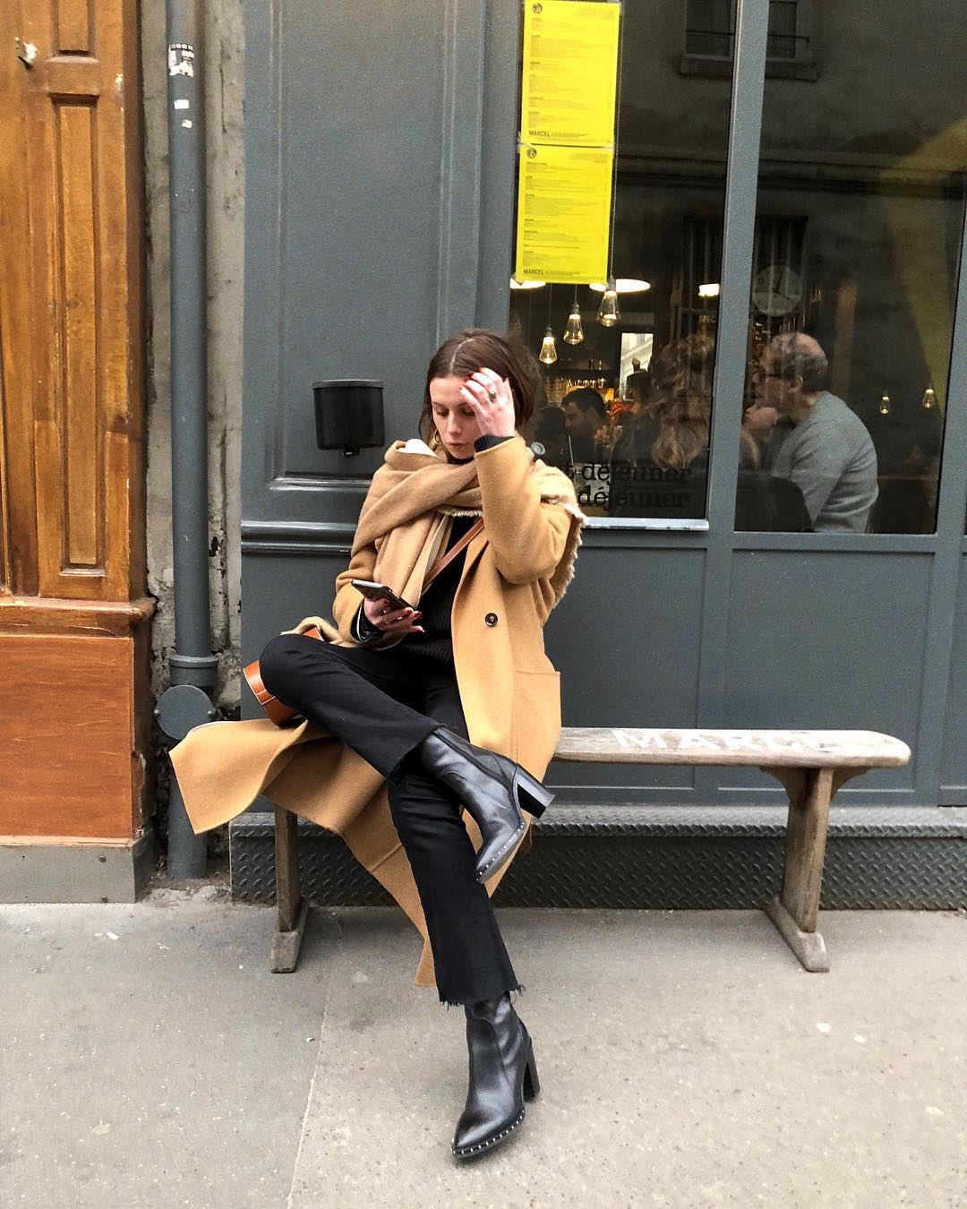 Stylish French-Girl Winter Outfit — @solenelara Instagram look with a camel coat, small tan bucket bag, black raw-hem jeans, and black studded ankle boots
