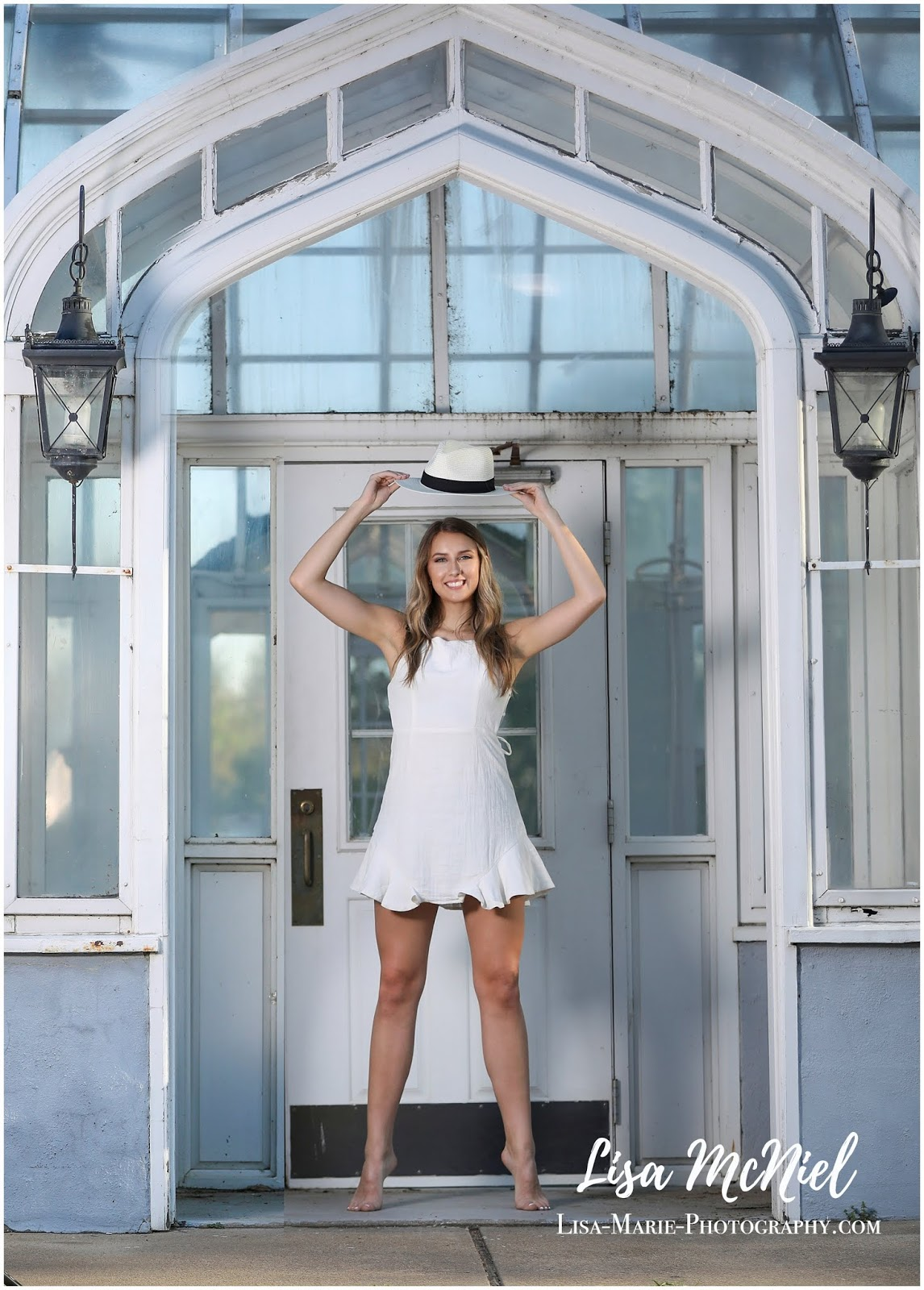 pretty teen girl in white dress in front of greenhouse
