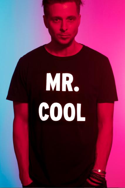 Cantor Ryan Tedder veste uma camiseta preta com frase em branca escrita Mr. Cool