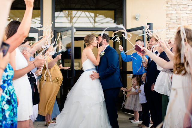 """A very special wedding took place on May 19, 2018…besides the one 'across the pond' with Prince Harry and Meghan!  After a five-year engagement, Liz and Chris tied the knot at Stillwater Bible Church, where the couple are regular attendees.      If there is one thing we know about Chris, it is that he is persistent.  Chris said it took him six months to get Liz to start talking to him after first meeting in a sophomore speech class in college.  But from then on, they have become inseparable.  Liz shared that Chris proposed to her at Sandborn Lake as they watched the multi-colored Oklahoma sunset disappear.  It was an """"intimate, private moment…special and perfect.""""  There's no doubt these two were made for each other.        On their wedding day, Liz was stunning in her strapless wedding gown, composed of light and airy tiers of tulle below a perfectly shaped bodice.  Her bridesmaids wore romantic, dusty blue chiffon gowns and carried white hydrangeas, while the bride's bouquet included white roses, baby's breath, snapdragons and hydrangeas with blue accent flowers.  Chris looked dapper in his royal blue suit, dusty blue tie, and two-tone brown, intricately stitched cowboy boots (the bride had cowboy boots on too).      After they exchanged vows, guests were invited to a reception buffet, the cake cutting, and the first dances.  The day was filled with heartfelt moments shared by the people they loved, and before long, the young couple departed amid a throng of well-wishers…headed for a romantic getaway honeymoon to Yellowstone and the Grand Tetons.  Wishing you two a lifetime of love and romantic nights watching the sunset by Sandborn Lake!"""