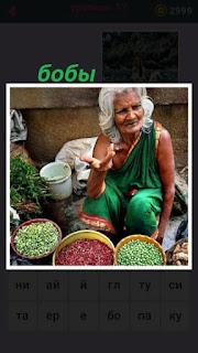 продавщица женщина продает бобы в мисках