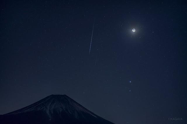 Hai vệt sao băng xuất hiện cùng Trăng lưỡi liềm và Sao Hỏa, Sao Mộc bên trên đỉnh núi Phú Sĩ. Geminid là một trong ba trận mưa sao băng đáng chú ý nhất trong năm, đêm qua chúng ta rất thuận lợi để quan sát được nó vì không có sự xuất hiện của Mặt Trăng mãi cho đến gần sáng. Hình ảnh: Kagaya Yutaka.