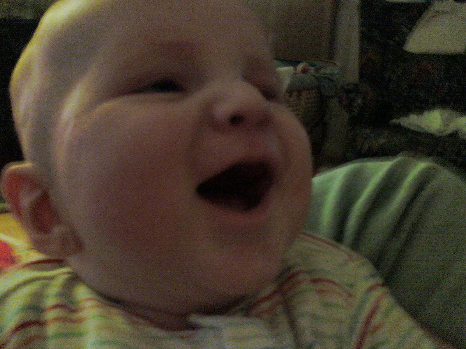 Baby Ieuan laughing in his highchair