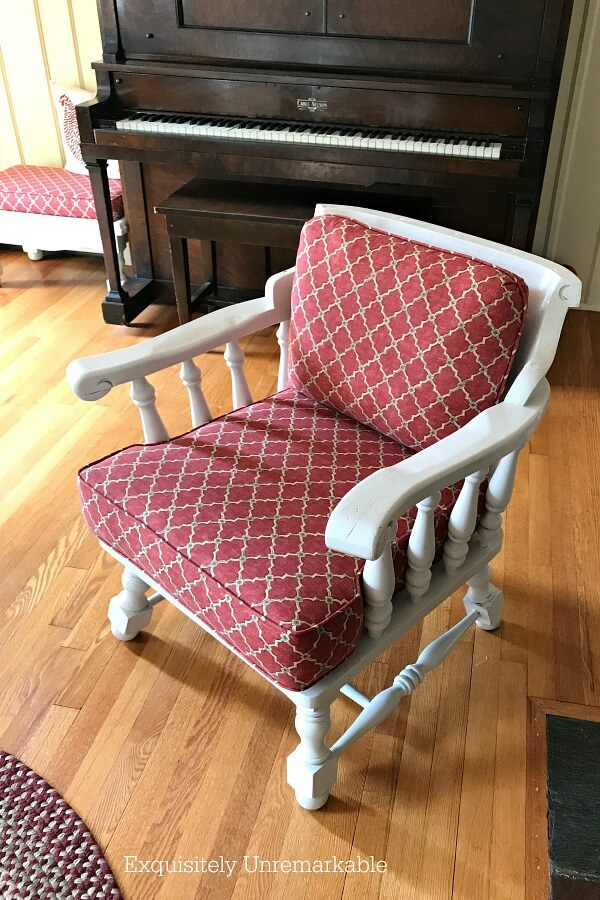 Painted Wooden Captain's Chair with red fabric cushions in a living room