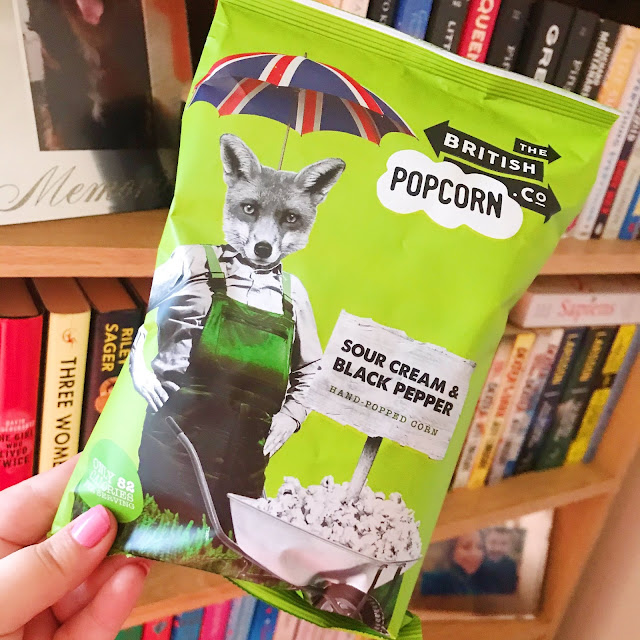 Sour cream & black pepper popcorn held up in front of bookshelf