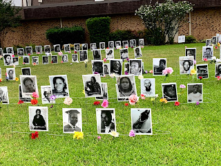 a portion of the many black and white headshots of Black people killed unjustly, each with flowers by it, on the lawn at a church