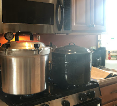 a pressure canner and water bath canner on the stove