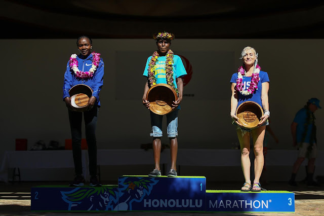 Top 3 finishers of the Women's race on the podium: Renee Metivier of the USA, 3rd place, Margaret Wanguri Muriuki of Kenya 1st place and Betsy Saina of Kenya 2nd place during the Honolulu Marathon 2019 on December 08, 2019 in Honolulu, Hawaii.