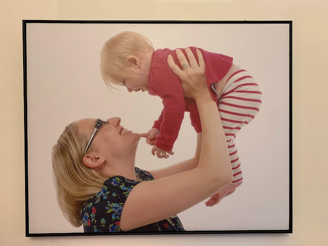 A framed canvas on the wall of a mother holding a small baby in the air