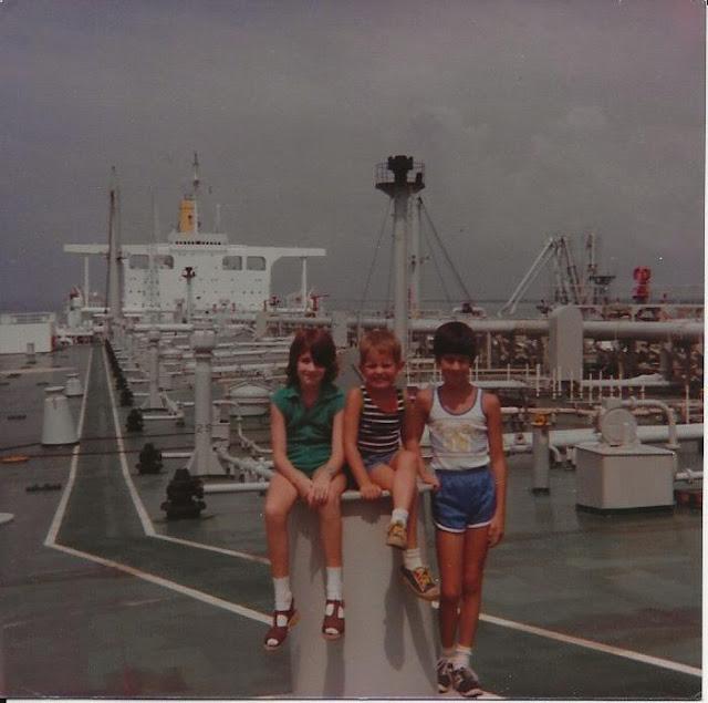 siblings sitting on deck of an oil tanker