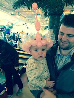 A baby girl wearing a beautiful balloon crown