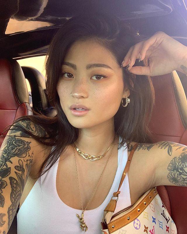 Una modelo tatuada conduciendo nos mira intrigada