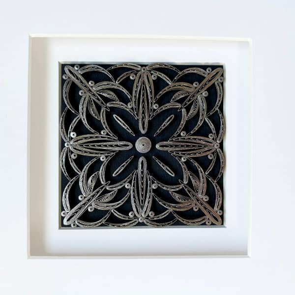 framed square white quilling design on dark background