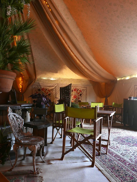Inside a marquee, with cast iron garden furniture and lots of plants