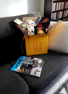 DHL carton of bags of chocolate on a sofa next to a copy of Home NZ magazine.