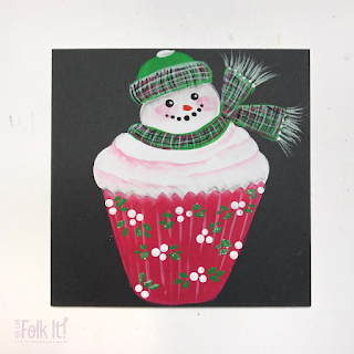 Handpainted snowman topped cupcake design Christmas card. Thesnowman wears a green tartan hat and scarf and the red cupcake wrapper is decorated with white berries and leaves