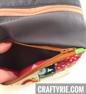 Fingers opening the front zipper section on the boxy pouch
