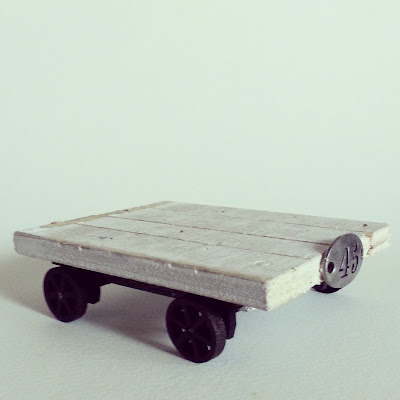 One-twelfth scale industrial-style trolley with rusted wheels and undercarriage and distressed white top planks.