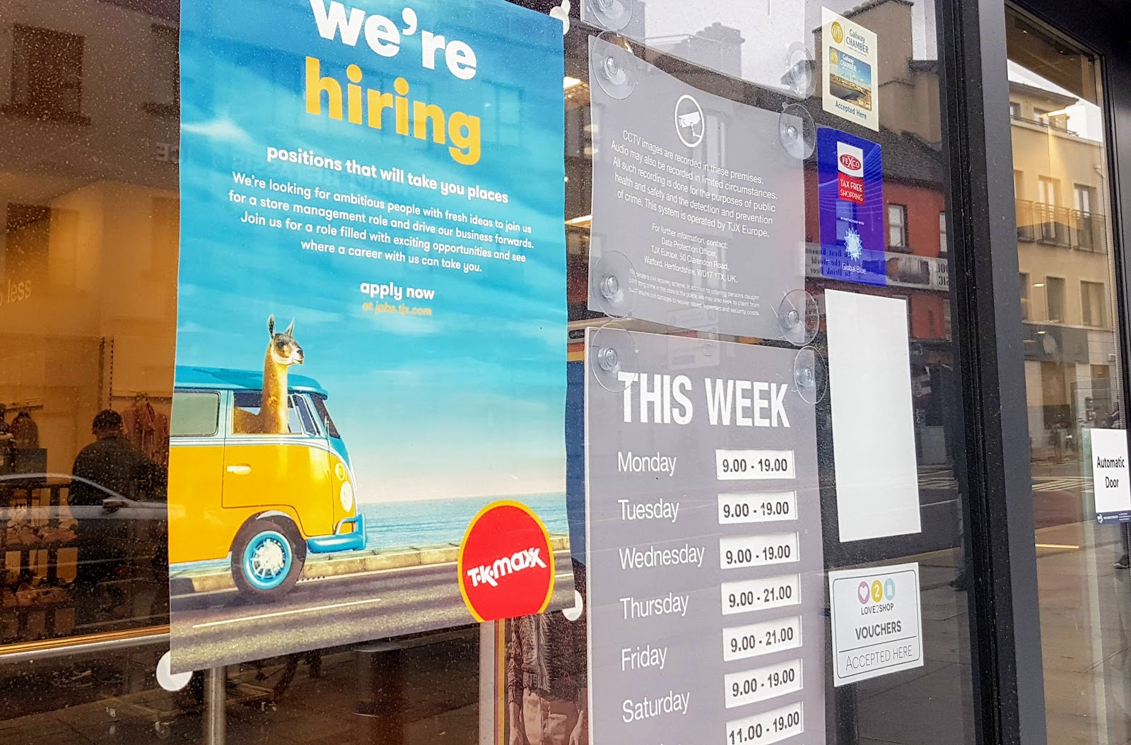 Sign showing the recruitment poster and the shop opening hours TK-Maxx Galway