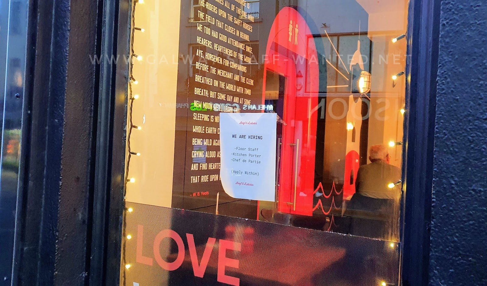 """restaurant window with job ad and part of the phrase """"love where you eat"""" - looking to through to wall-to-ceiling poetry and a circular bright red restroom door"""