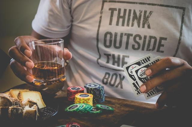 homem de camiseta branca segurando copo de cachaça e baralho de poker