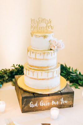 white and gold wedding cake on wooden stand