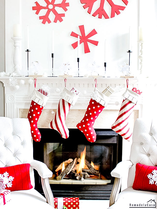 Red and white Christmas mantel with wooden snowflake art