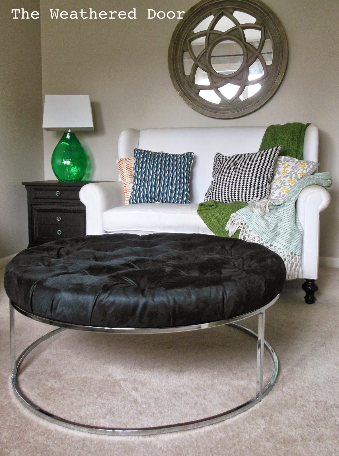 A Round Black Tufted Ottoman With Chrome Base