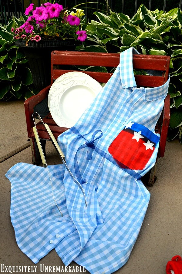 Patriotic Flag Men's Dress Shirt Apron on a red bench with a bbq prong