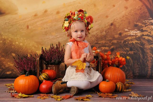 Uśmiechnięta mała dziewczynka w jesiennej stylizacji na sesji
