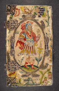 A color photograph of an elaborately embroidered book cover featuring the figure of a man and decorated with various insects and plants. There are metal ornaments and hinges visible.