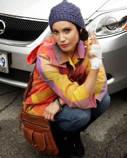 Carly Pope posing for picture with car in the background