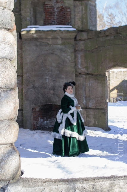 the author wearing a green velvet 170s bustle with fur trim and a gray hat in a ruined stone tower
