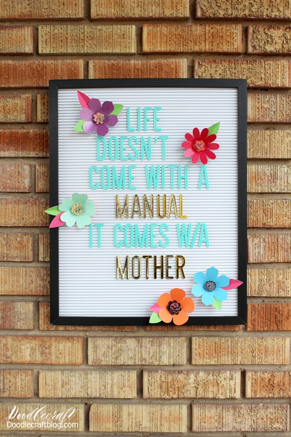 "White letterboard with aqua and gold letters reading ""life doesn't come with a manual, it comes with a mother"" decorated with brightly colored paper flowers cut using the cricut maker."