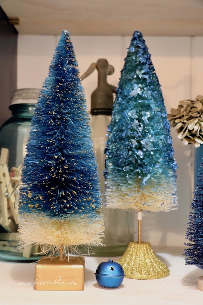 Blue Christmas Laundry Room open shelves decorated with blue bottle brush trees that match the antique blue seltzer bottle from a Paris flea market