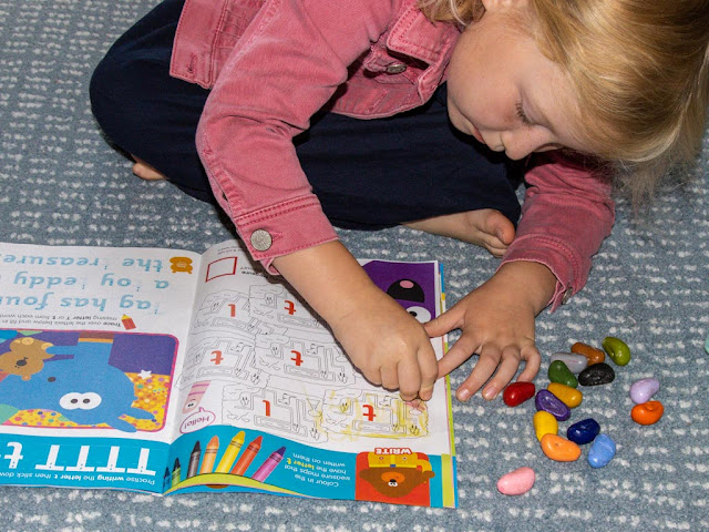 a girl colouring in treasure maps with the letter t on them in a magazine
