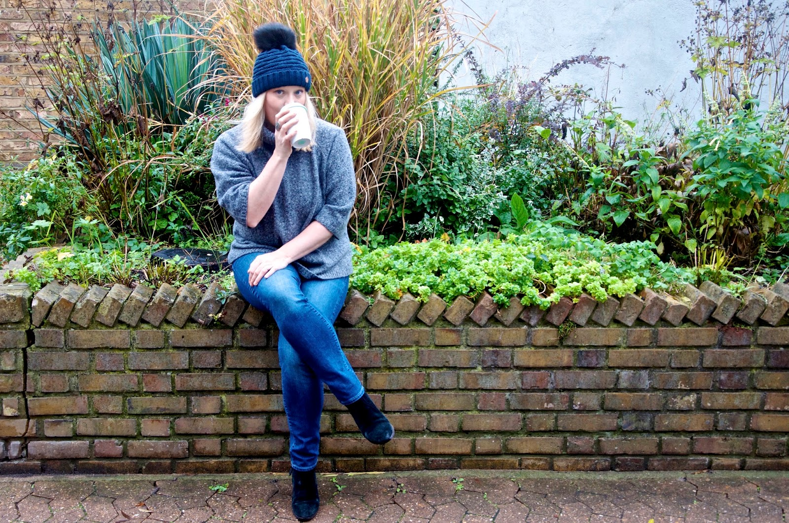 Brick Fence, garden, plants, grey sweater, blue jeans, black boots and navy hat