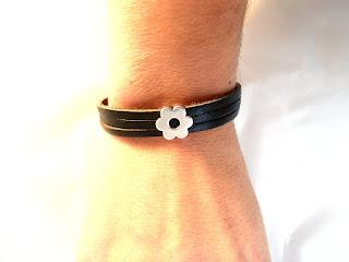 Vue sur un bras du bracelet cuir noir décoré d'un motif fleur