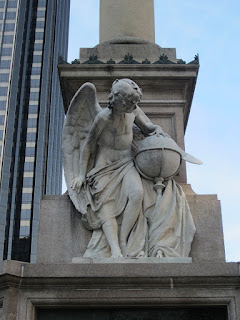The angel holding a globe on the pedestal of the Christopher Columbus Monument